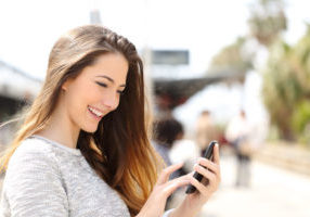 40317243 - happy girl texting on a smart phone in a train station while is waiting