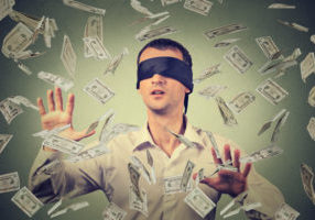 55040329 - blindfolded young businessman trying to catch dollar bills banknotes flying in the air isolated on gray wall background. financial corporate success or crisis challenge concept